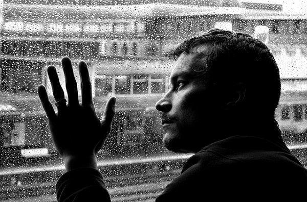 窓に手を当て絶望する男性