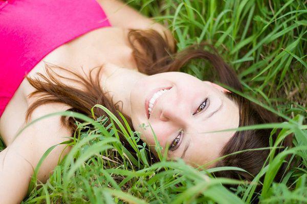草むらに寝そべる女性