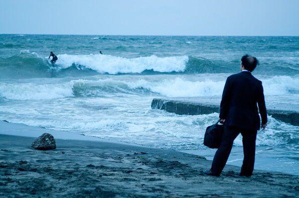 海にたたずむサラリーマン