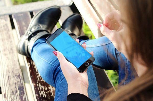 ベンチでiPhoneを操作する女性