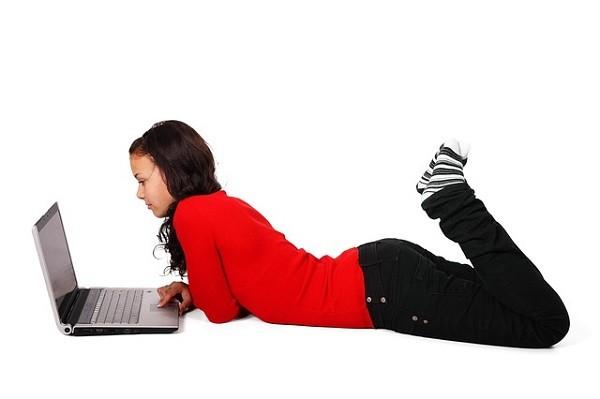 床でインターネットをする少女