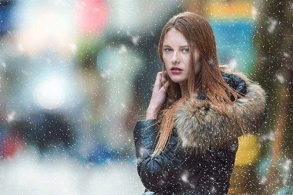 粉雪とフードの女性