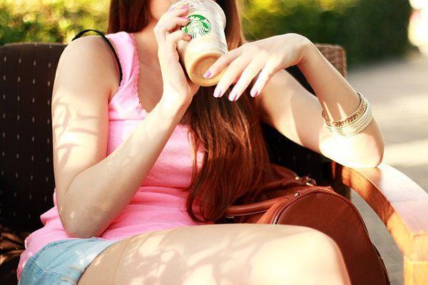 ベンチでアイスラテを飲む女性