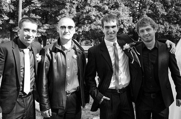 胸に花をつけた男性4人組