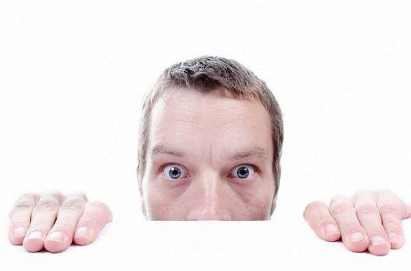 恐るおそる机から顔を出す男性