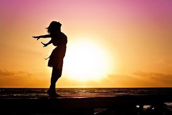 夕日を背に深呼吸する女性