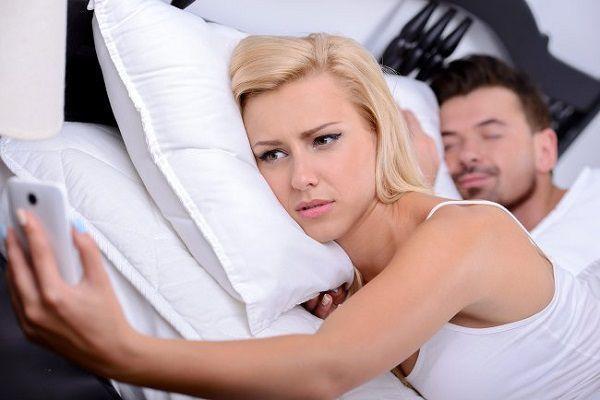 ベッドで携帯を触る女性