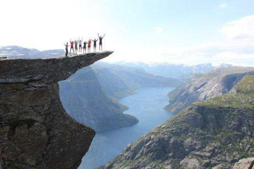 今にも折れそうな岩の上でジャンプする人々
