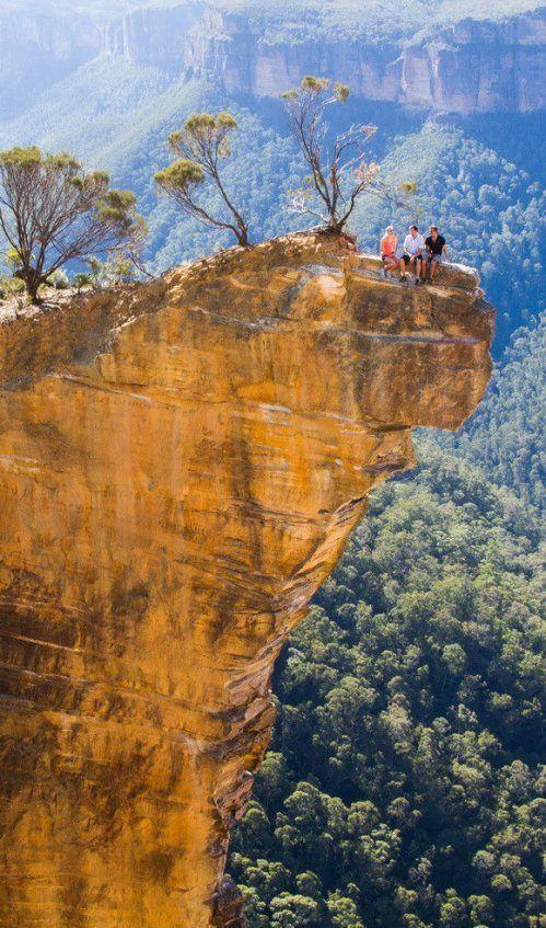 とんでもない崖の上で座る人々