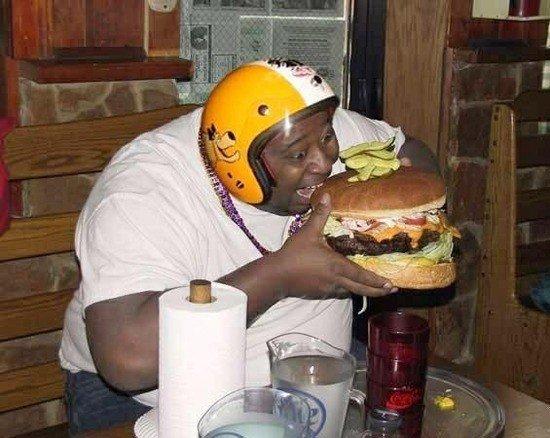 巨大ハンバーガーにかぶりつく男性