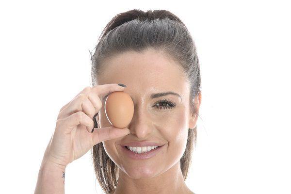 卵で片目を隠す女性