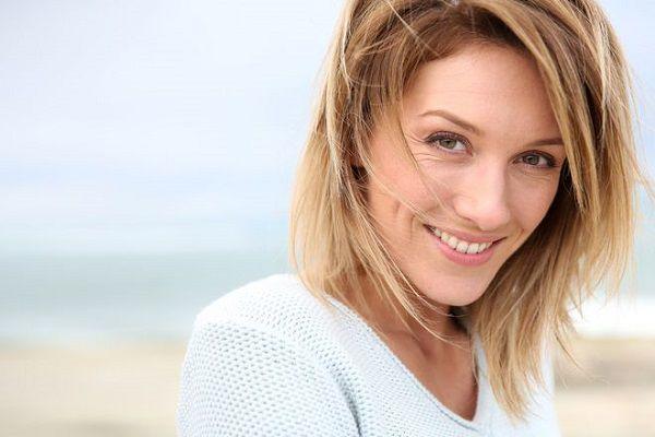 海辺で優しく微笑む年長の女性