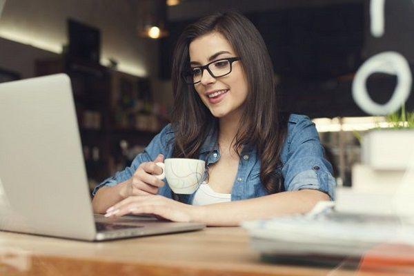 コーヒーを飲みながらPCを触る女性