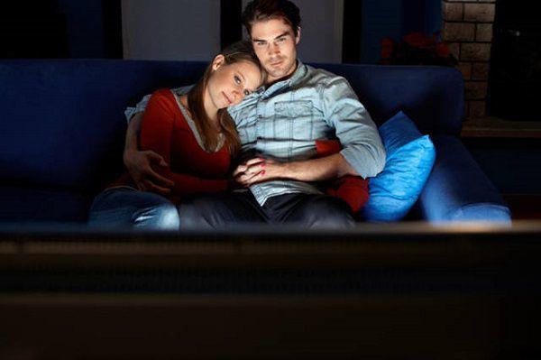 部屋でオンライン映画を観るカップル