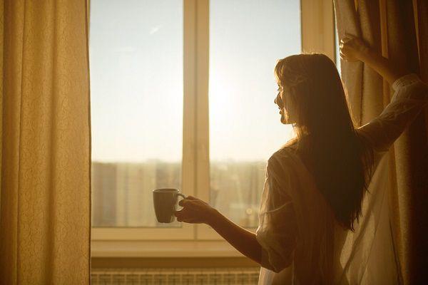 朝、カーテンを開けて陽の光を浴びる女性