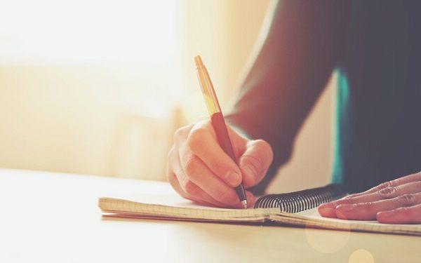 ノートに書き出す女性の手元