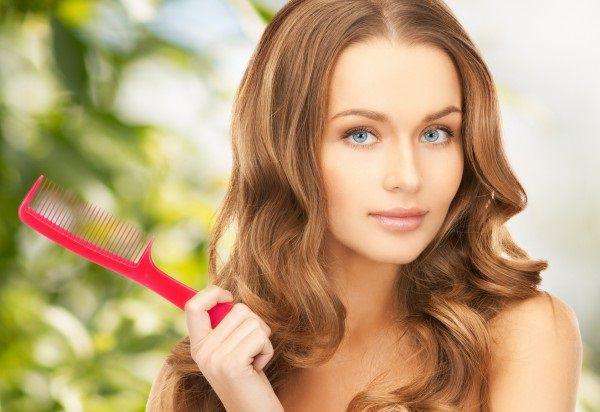 くしを持つ抜け毛に悩む女性