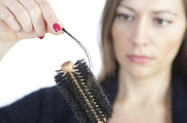 ブラシについた抜け毛をつまむ女性