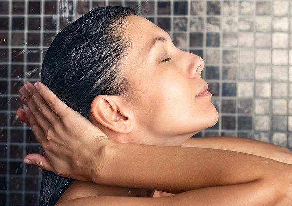シャンプーを洗い流す女性
